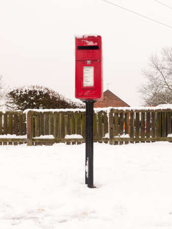 red village post box outside street village with snow winter; essex; england; uk