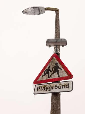 triangle road sign pole street lamp children snow winter; essex; england; uk Stock Photo