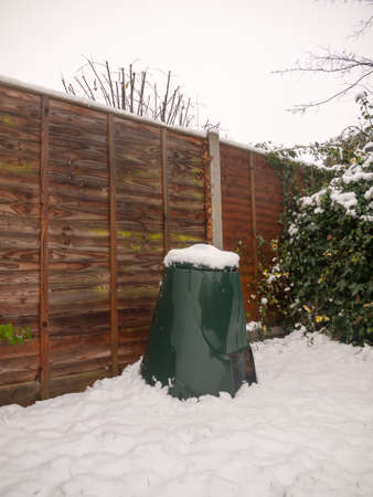 snow in back garden on green bin lid and fence and floor; essex; england; uk