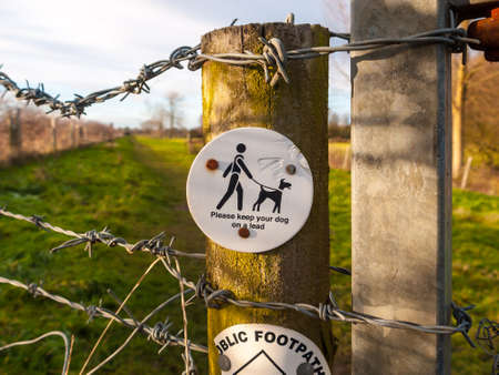 close up of please keep your dog on a lead circle white and black country walk sign post; essex; england; uk 写真素材