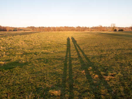two human silhouettes large legs field of grass background; essex; england; uk