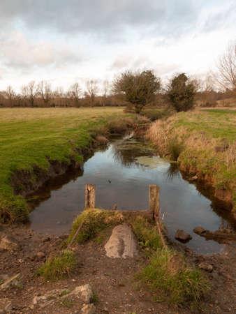 wet waterlogged country farm land stream eddy ; essex; england; uk Stock Photo - 95684550