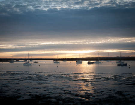 sunset over river estuary west mersea essex seafront coast boats; essex; england; uk Stock Photo