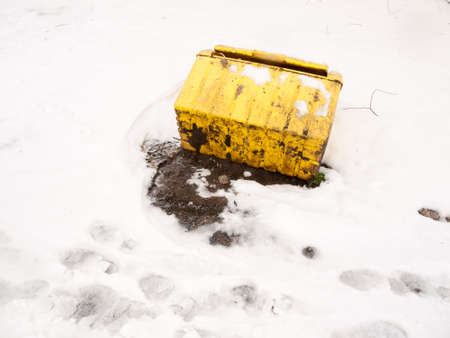 fallen turned over yellow grit box salt outside snow storm; essex; england; uk