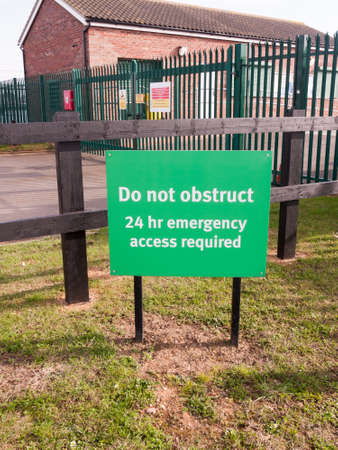 green sign do no obstruct 24 hr emergency access required ; essex; england; uk 版權商用圖片