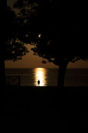 silhouette of a man against the sea at sunset with reflections in the water