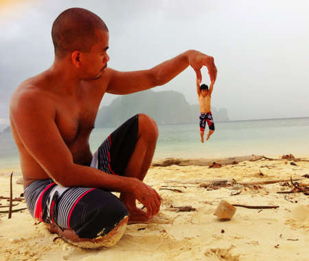 giant man: A perfectly timed photo of a giant holding up a small man, El nido, Palawan, Philippines
