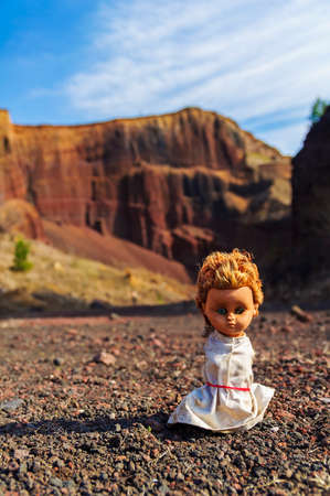 Broken doll  lying on the ground in a volcano crater photo