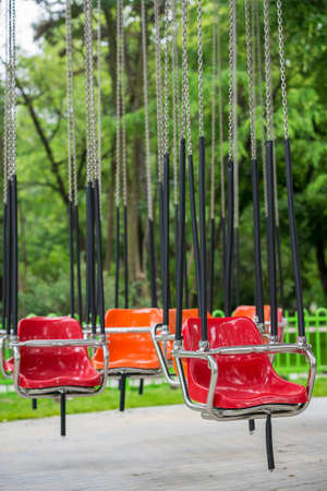 chain swing ride: Empty colorful swinging chairs Carousel in standby