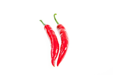 intense flavor: Two fresh red chilies close up on with background Stock Photo