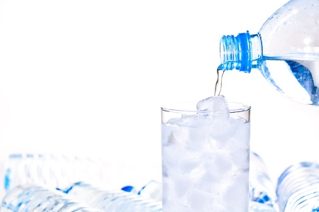 Glass of ice water being filled with a water bottle Stock Photo