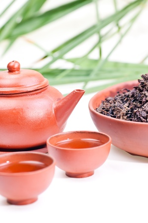 Chinese tea in clay cup close up with tea set and chinese tea leafs in a bowl photo