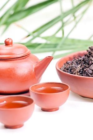Chinesische Tee-Becher aus Ton hautnah mit Tee-Set und chinesischen Teebl�tter in eine Sch�ssel geben