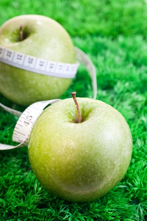 Two green apples on grass with tape measure for fitness concept photo