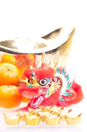 Chinese new year with dragon decoration, large gold ingot and mandarin oranges photo