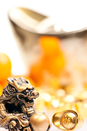 chinese new year dragon: Chinese new year with large ingot, mandarin oranges and dragon statue close up Stock Photo
