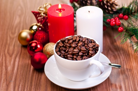 Christmas cup of coffee beans with candles and ornaments over wood background photo