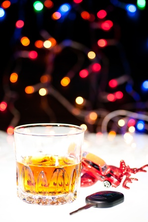 Glass of whiskey, a car key and a toy car over a rain deer with lights at the background photo