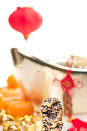 Close up of dragon for chinese new year with mandarin oranges, ingots, lantern and old fortune chinese coins at background photo