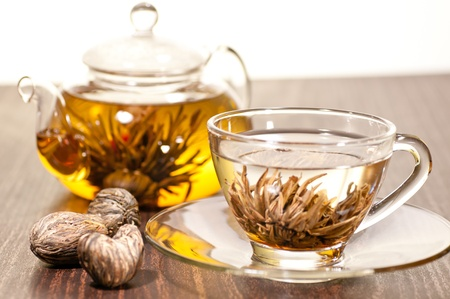 Blooming green tea in glass teacup close up with teapot  various dry blooming tea on the table photo