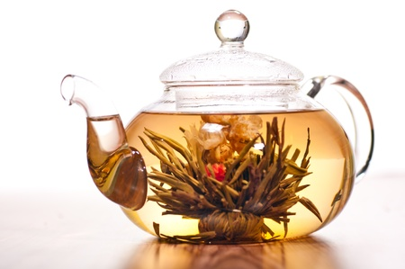 Blooming green tea in glass teapot on a wooden table