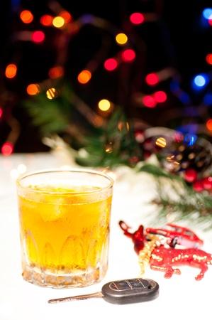 Glas Whiskey mit Eis, ein Autoschl�ssel und ein Spielzeugauto �ber ein Rentier mit Lichtern in den Hintergrund