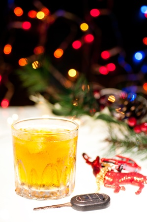 Glass of whiskey with ice, a car key and a toy car over a reindeer with lights at the background