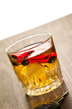 Dont drink and drive concept with a toy car in a glass on whiskey photo
