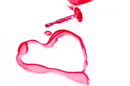 Nail polish with heart shape symbol over white background photo