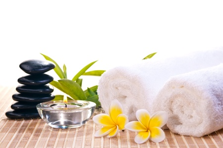 Spa concept with black zen stones, flowers on bamboo mat background Stock Photo
