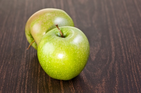 Two fresh and juicy apples on a dark wooden table photo