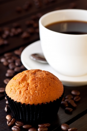 Coffee with a muffin on table close up photo
