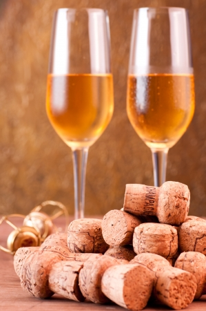 Pile of champagne corks with two glasses of champagne at the background photo