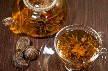 Blooming tea close up in a glass cup on a wooden table photo