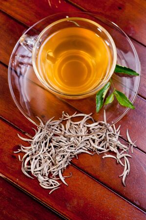 tip of the leaf: A cup of silver tips tea on teak wood table Stock Photo