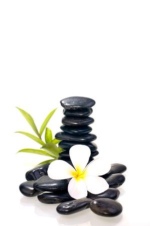 Stapel von vielen schwarzen zen Stein mit wei�en Plumeriablume