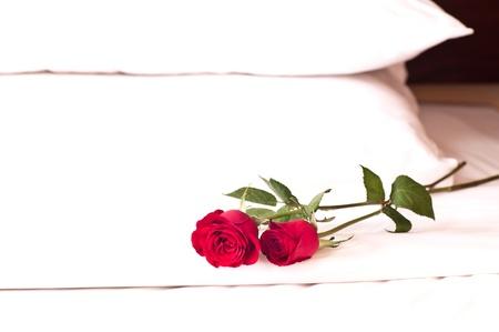 Romantische Einstellung auf einem Bett mit roten Rosen