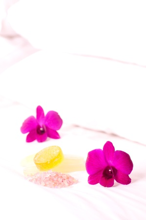 Spa concept orchids, bath soap and bath salt on hotel bed close up photo