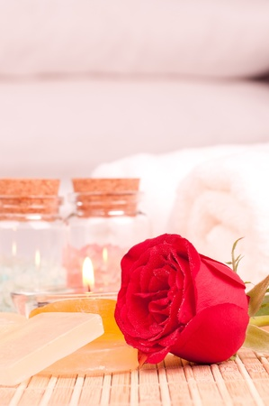 Romantic spa getaway with a red rose, bath salt and pillows background