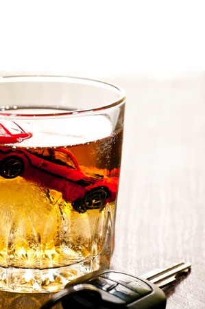 Toy car in a glass of whisky close up with a don t drink and drive concept