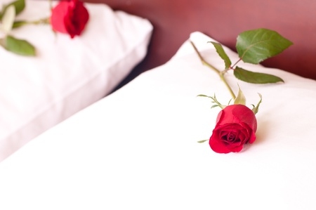 Romantic getaway with red rose on pillow