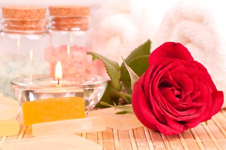 Romantic spa break with a red rose on a bamboo mat close up