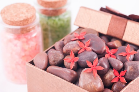 Spa concept - a gift of wellness with red zen stones and flowers photo