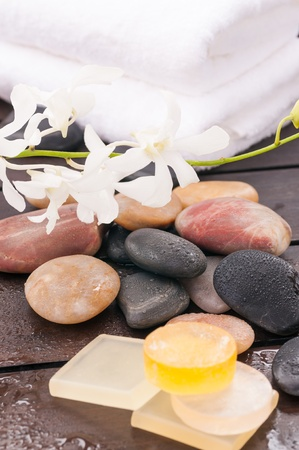 Outdoor spa concept with orchids and river stones close up photo