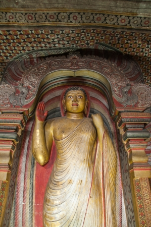 Golden Buddha close up at Dambulla Cave Temple, Sri Lanka  Unesco World Heritage Site  photo