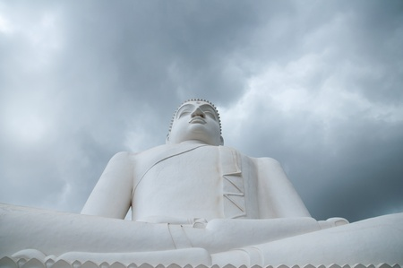 Meditating Buddha statue with clouds background at Athugala, Sri Lanka photo