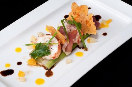 comida gourmet: Medallón de langosta con jamón y salsa de espárragos cítricos, aderezo balsámico y galleta de parmesano Foto de archivo