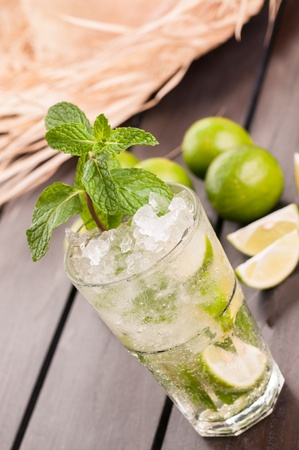 Mojito cocktail with a straw hat on an outdoor wooden table in the garden  photo