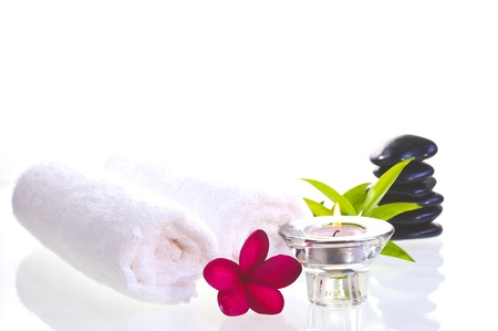 Spa concept with black zen stones and red Frangipani flower over white background photo