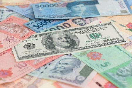 American one hundred dollar bill and Asian currencies background